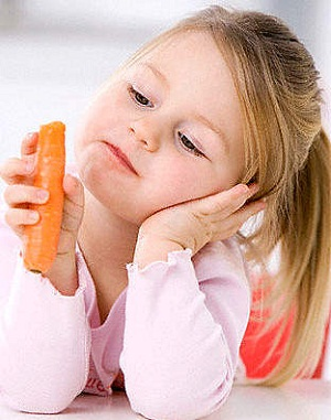 Little girl (3-4) holding a carrot, portrait